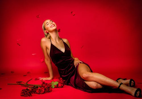 Woman in Spaghetti Strap Dress Posing in a Red Background