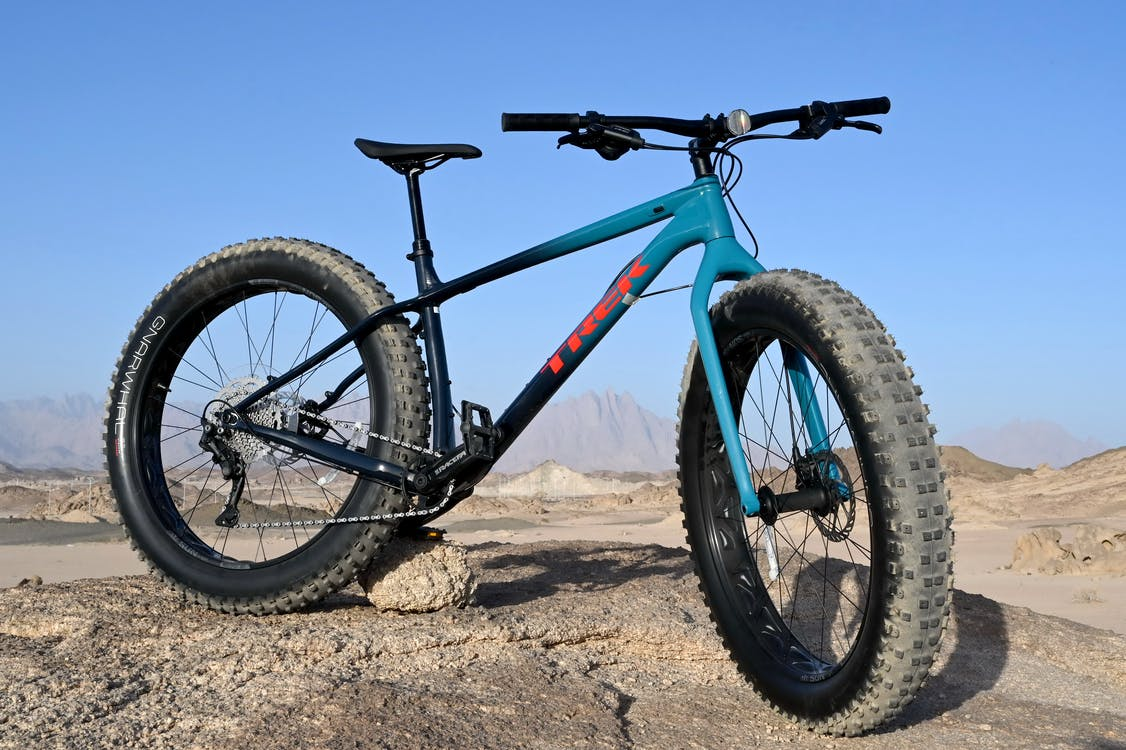 Black and Blue Mountain Bike on Brown Sand