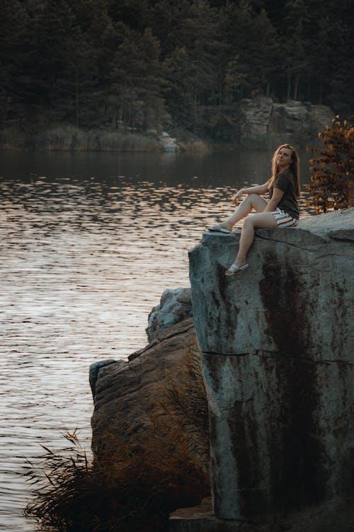 A Woman Sitting on Top of a Rock Near a Lake