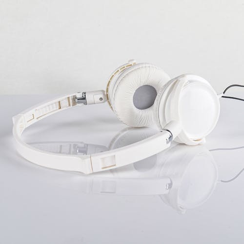 Close-Up Shot of White Headphones on a White Surface