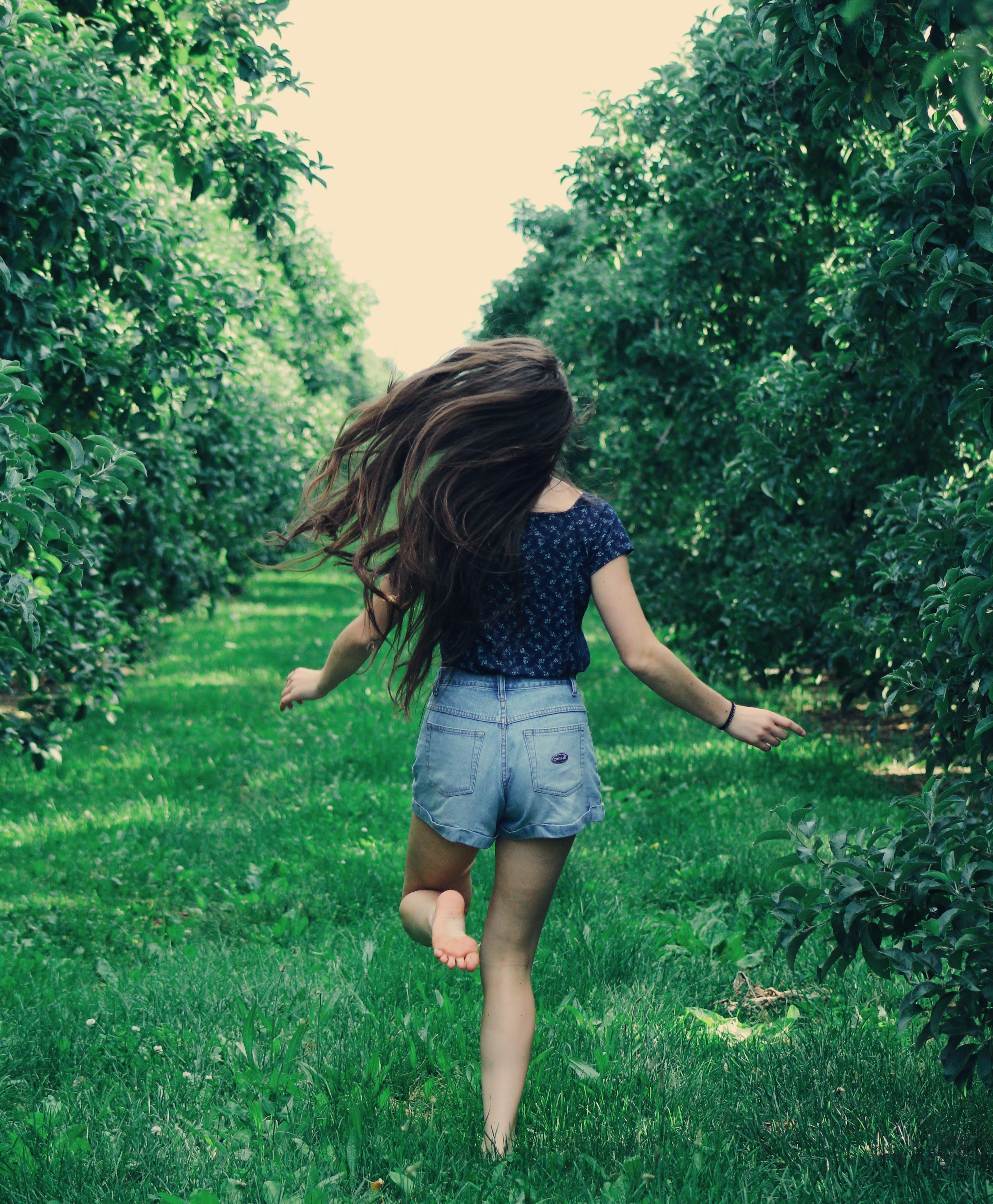 Photo of a Woman Running on Green Grass