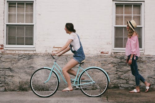 Woman Riding on Teal Cruiser Bike Near Woman Wearing Pink Long-sleeved Shirt
