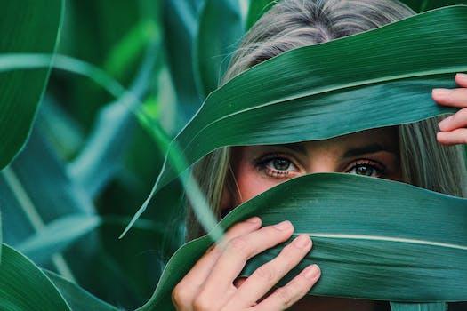 Mulher cobrindo o rosto com folhas de milho
