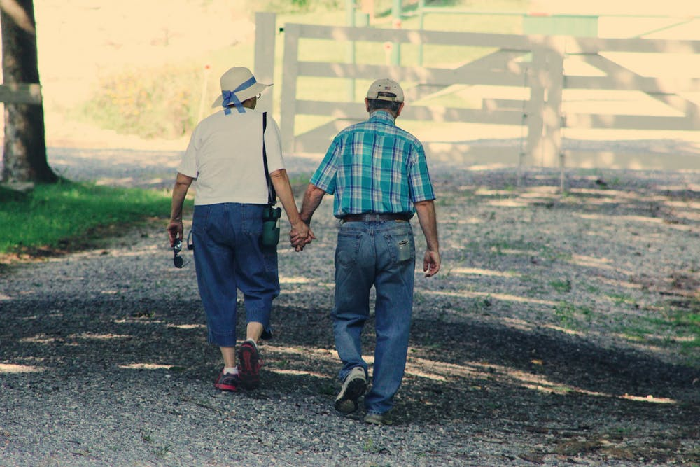 Old couple walking while holding hands. | Photo: Pexels