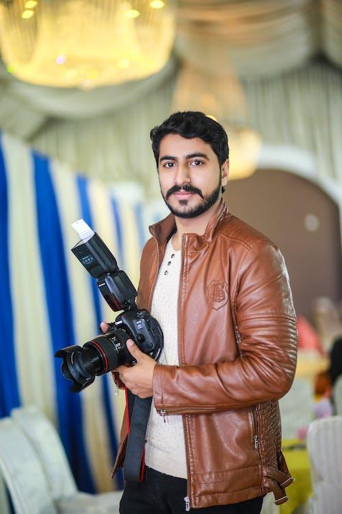 Man in Brown Leather Jacket Holding Black Dslr Camera