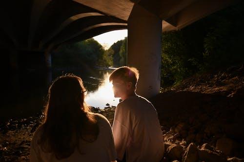 Man and Woman Sitting on Rocks Under a Bridge