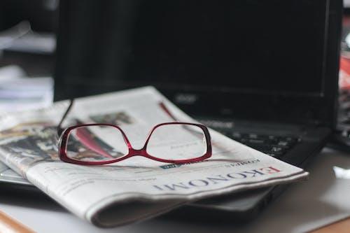Red Eyeglasses on Top of a Newspaper