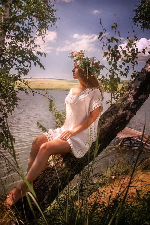 Woman in White Dress resting on a Tree Branch