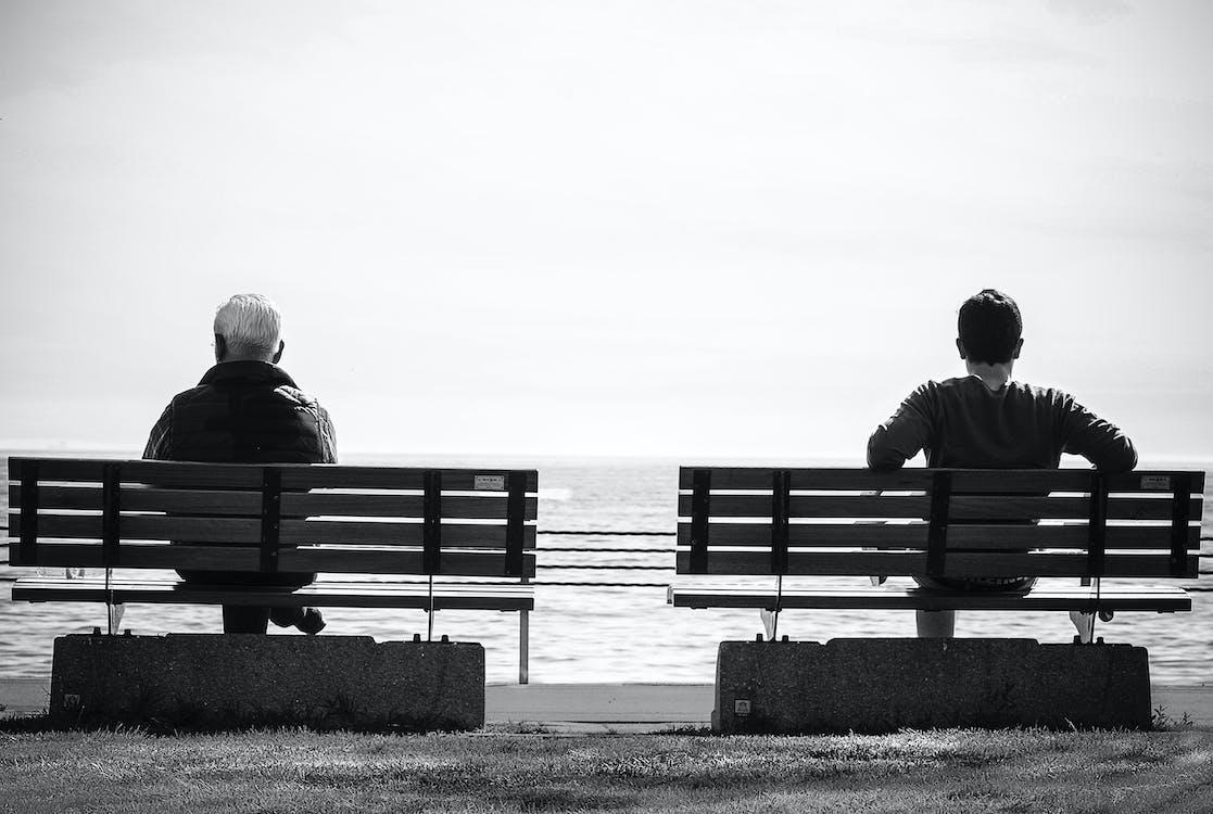 Foto En Escala De Grises Para 2 Personas Sentadas En Bancos Separados Junto Al Mar
