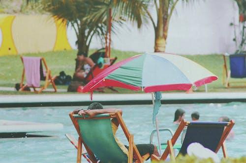躺在游泳池旁的長椅上的人