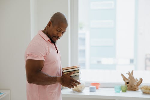 Man in Pink Polo Shirt Holding Books