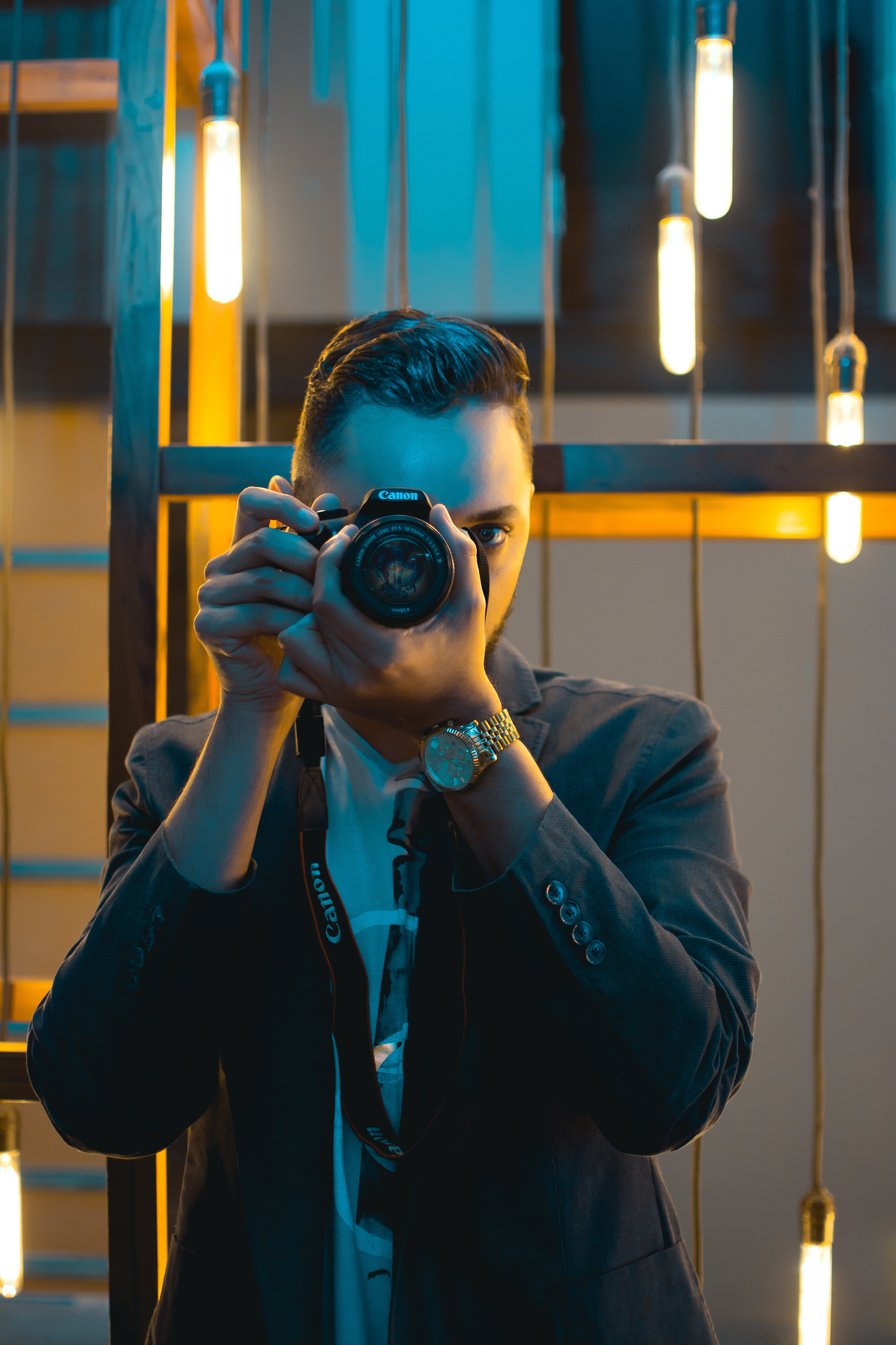 Man in Black Suit Holding Canon Dslr Camera