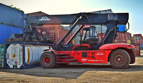 Red and Black Front-loader Beside Intermodal Containers