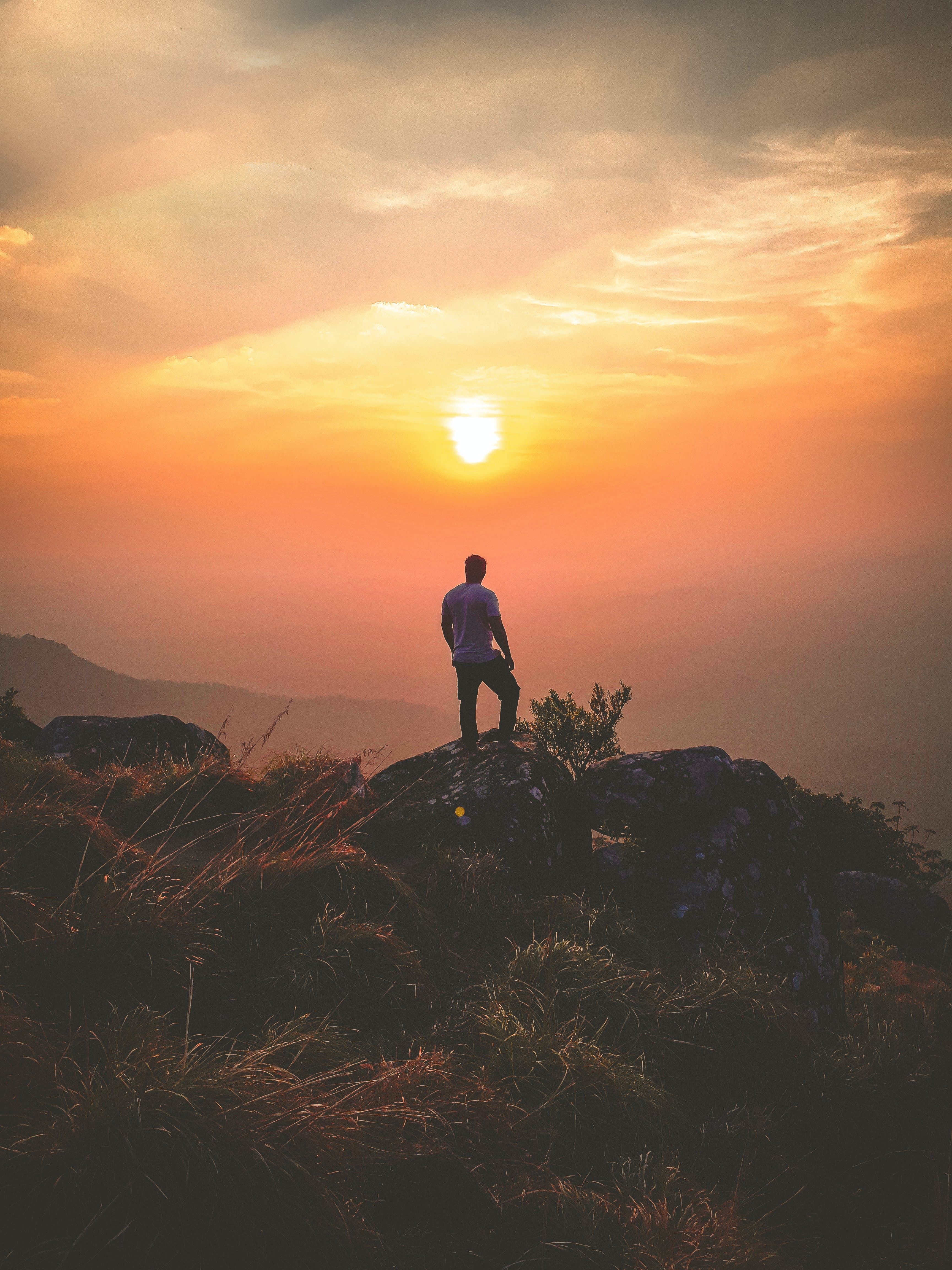 Man Standing on Rock During Sunset