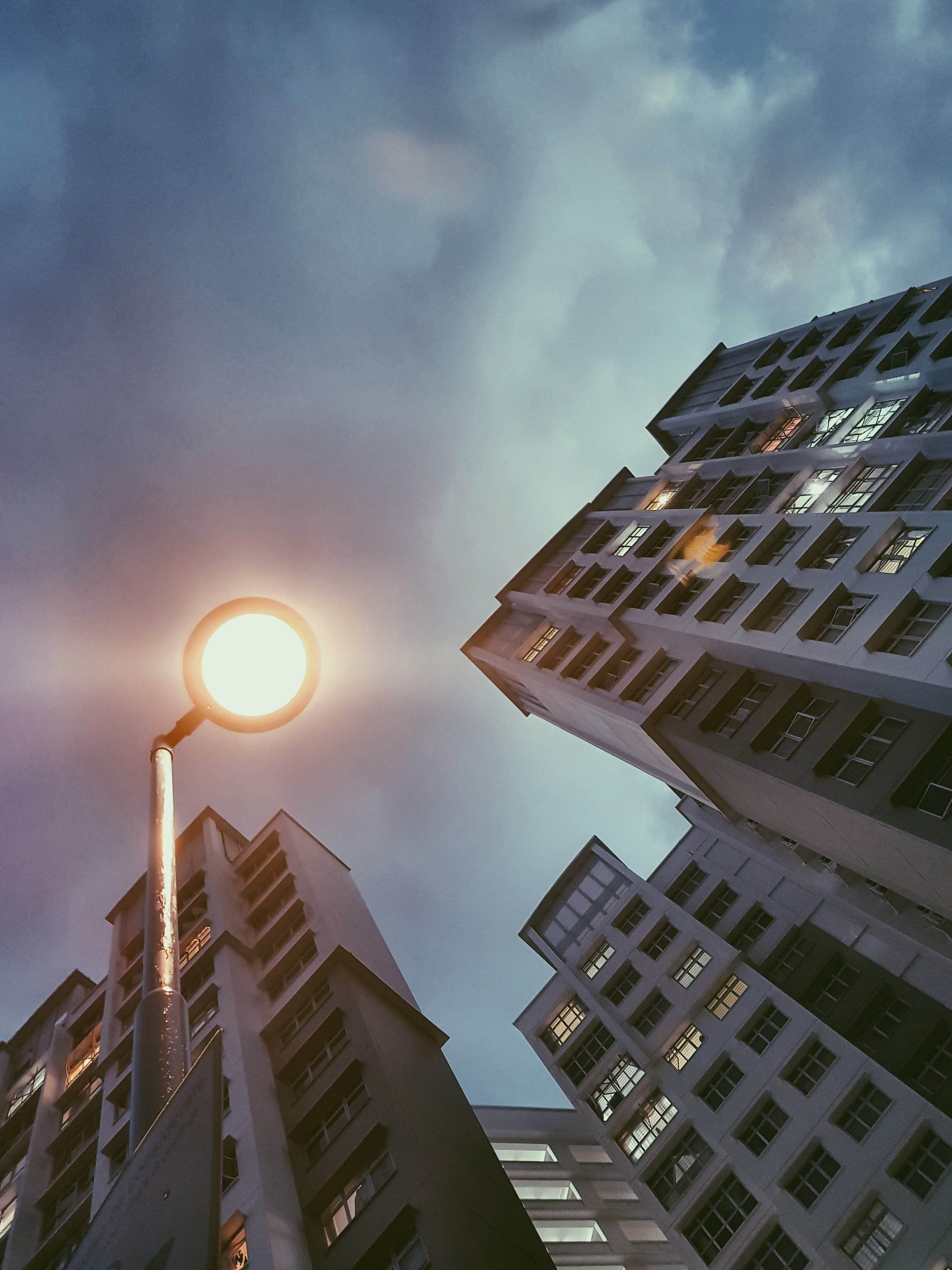 Low Angle Photography of Lamp Post Beside Building Under Cloudy Sky