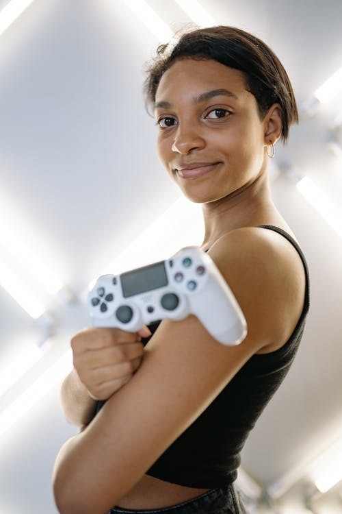 Woman in a Black Tank Top Holding a White Game Controller