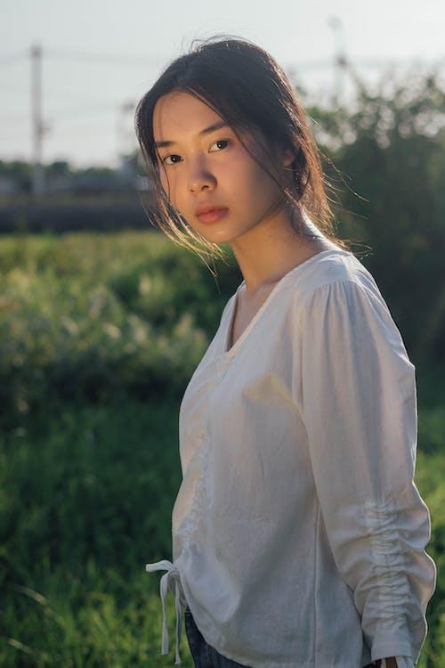 Woman in White Long Sleeve Shirt Standing Near Green Grass