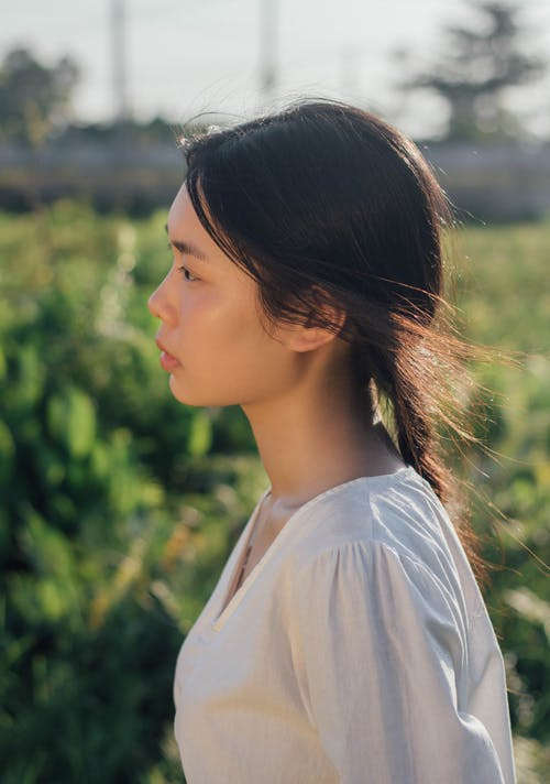 Woman in White Shirt Standing Near Green Grass