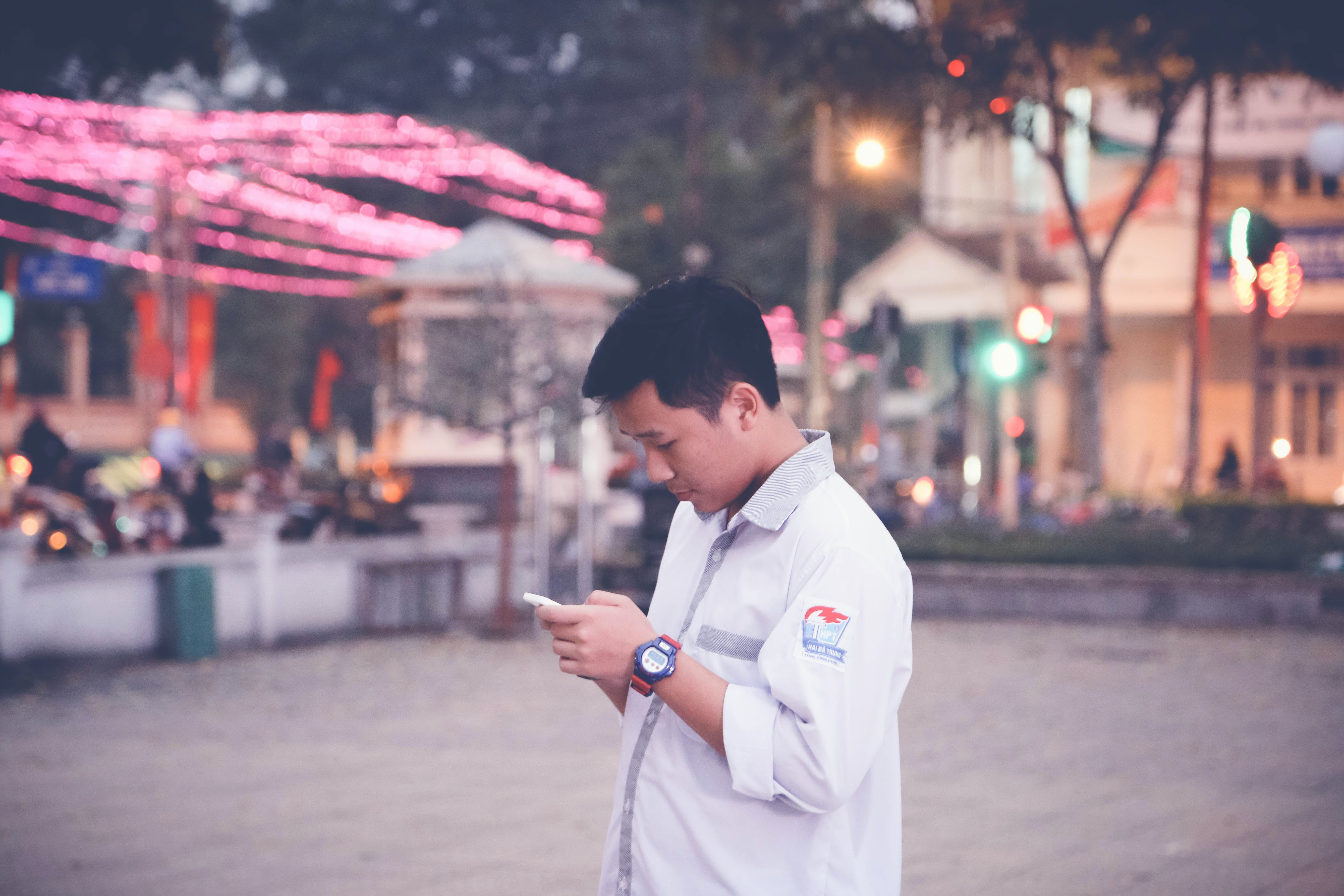 Focus Photography of Man Wearing White Sports Shirt Holding Smartphone Near Buntings