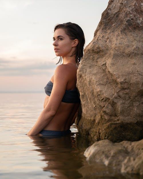 A Woman in a Bikini Leaning on a Rock
