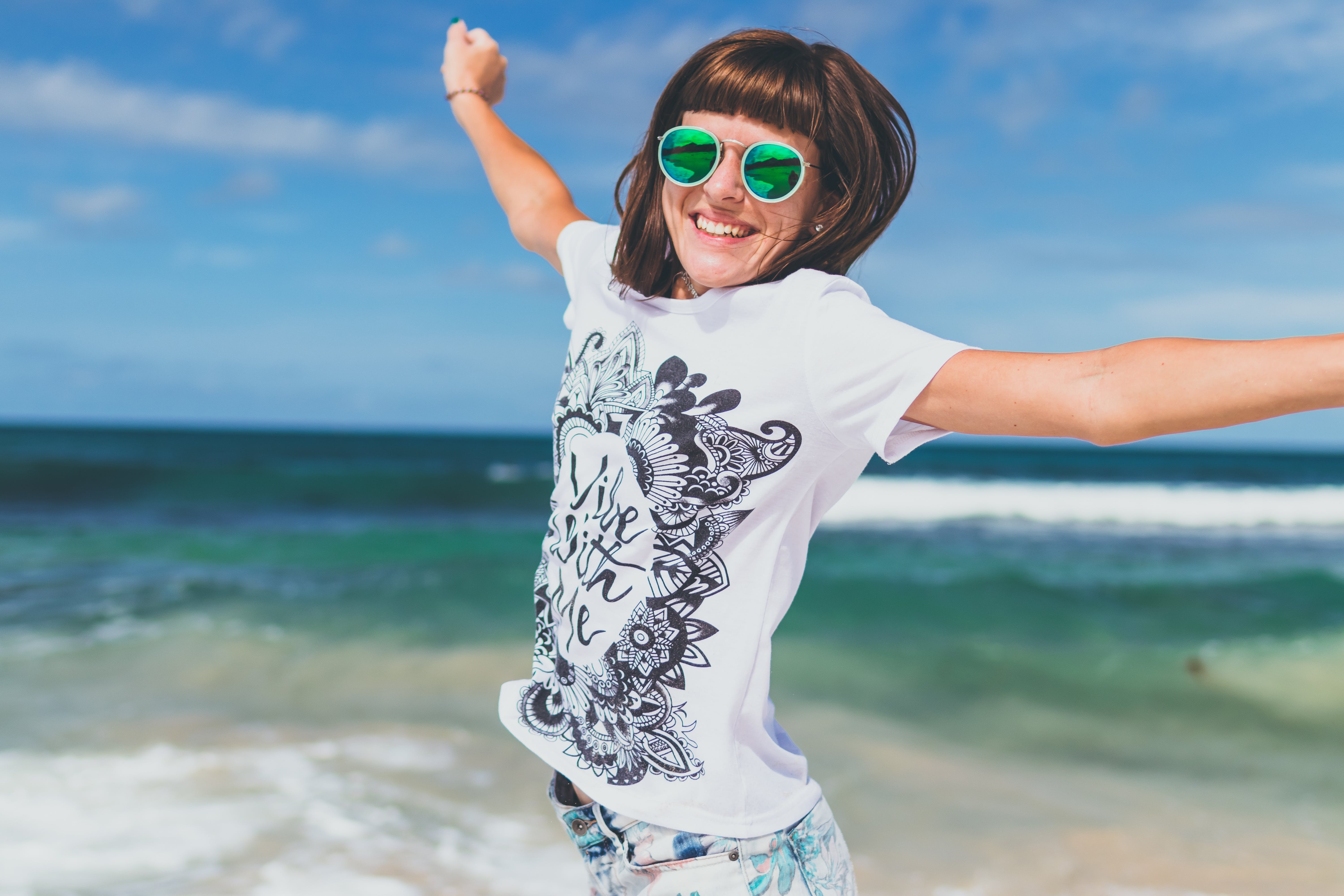 Woman in White and Black T-shirt Lifting Hands Smiling on Seashore