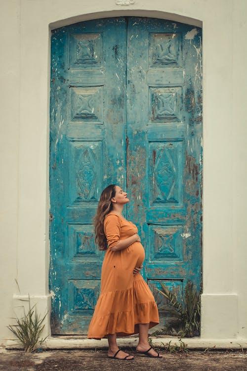 Woman in Orange Dress Standing in Front of Blue Wooden Door