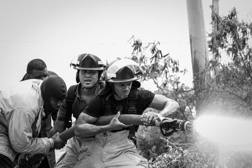 A Grayscale Photo of Firefighters Holding a Fire Hose