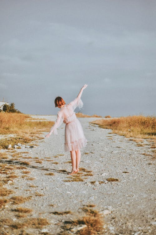 Woman Wearing Pink Dress Standing on Sand
