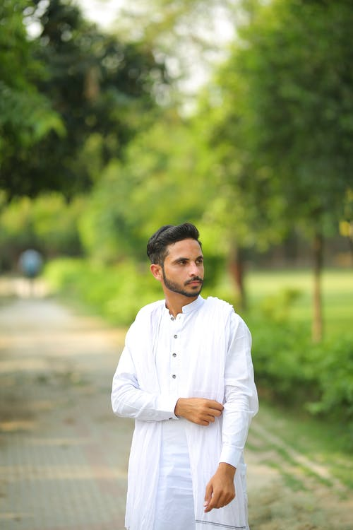 Man in White Dress Shirt Standing on Road