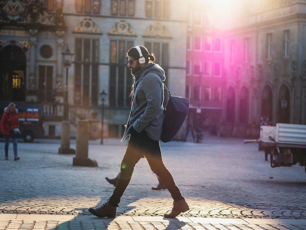 Man in Gray Hooded Jacket Walking on Gray Bricks Pavement