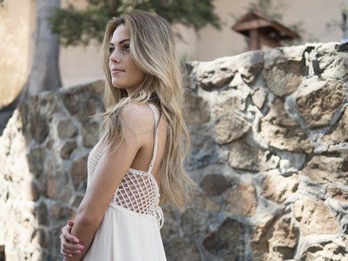 Blonde Haired Woman in White Dress Near Rock Wall in Daytime