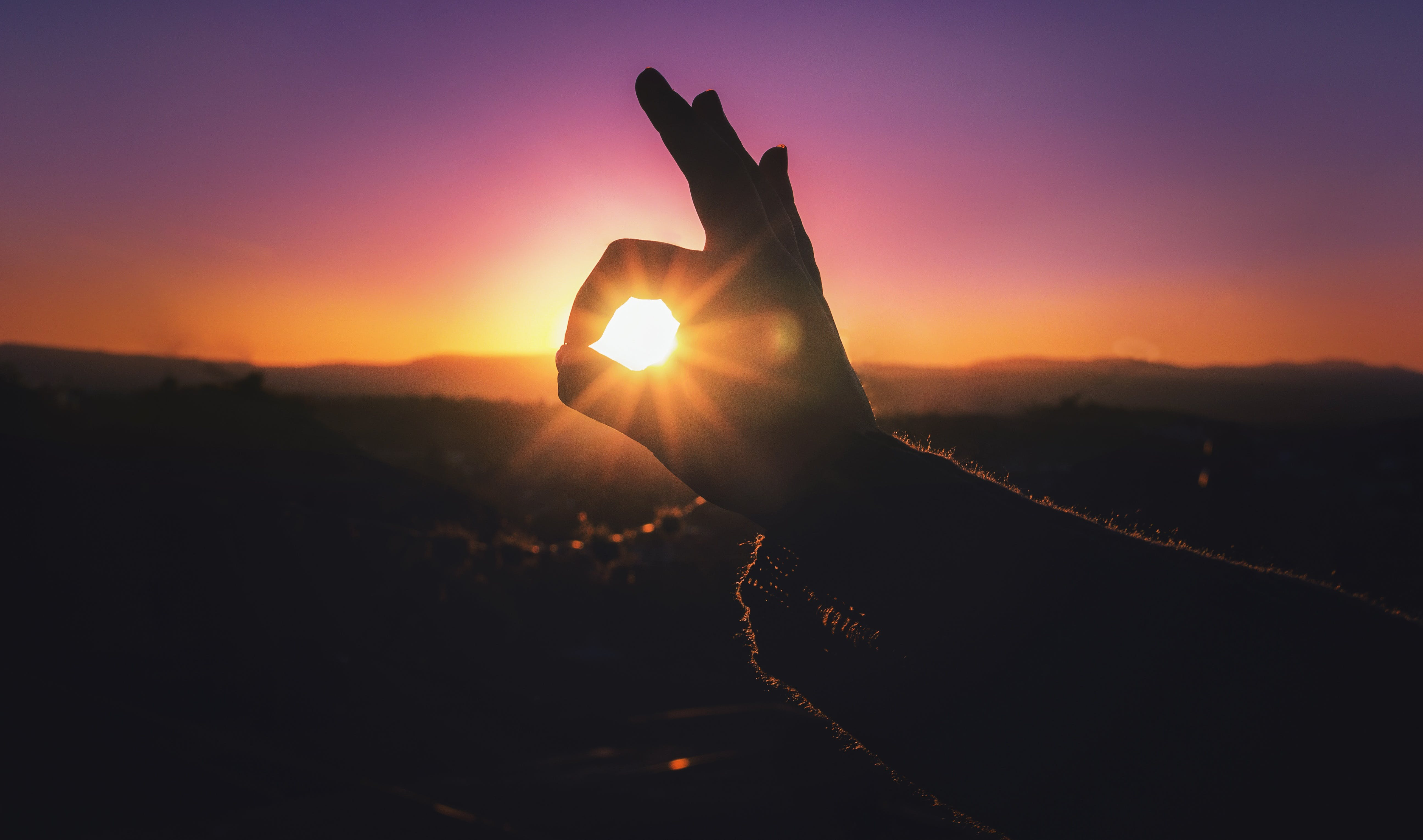 Person Doing Ok Hand Sign during Sunset