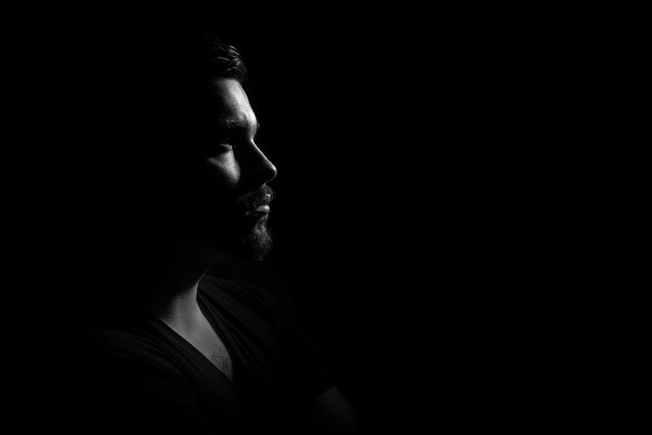 Grayscale Photo of Man in Black V Neck Shirt With Black Background