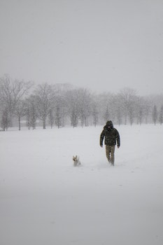 Photo of Man Wearing Black Jacket and Pants Walking on Snow