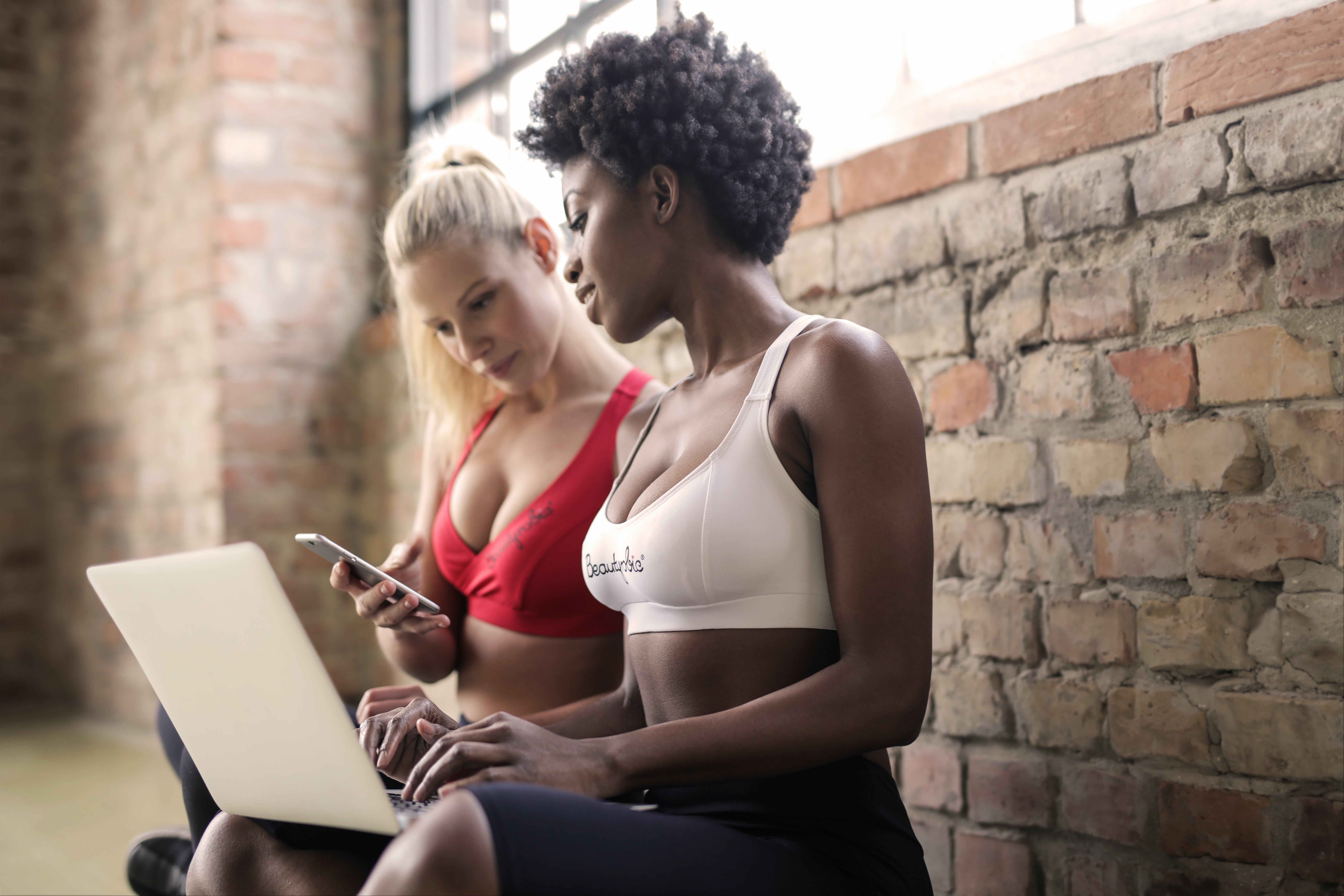 Two Woman Wearing Red and White Sports Bras