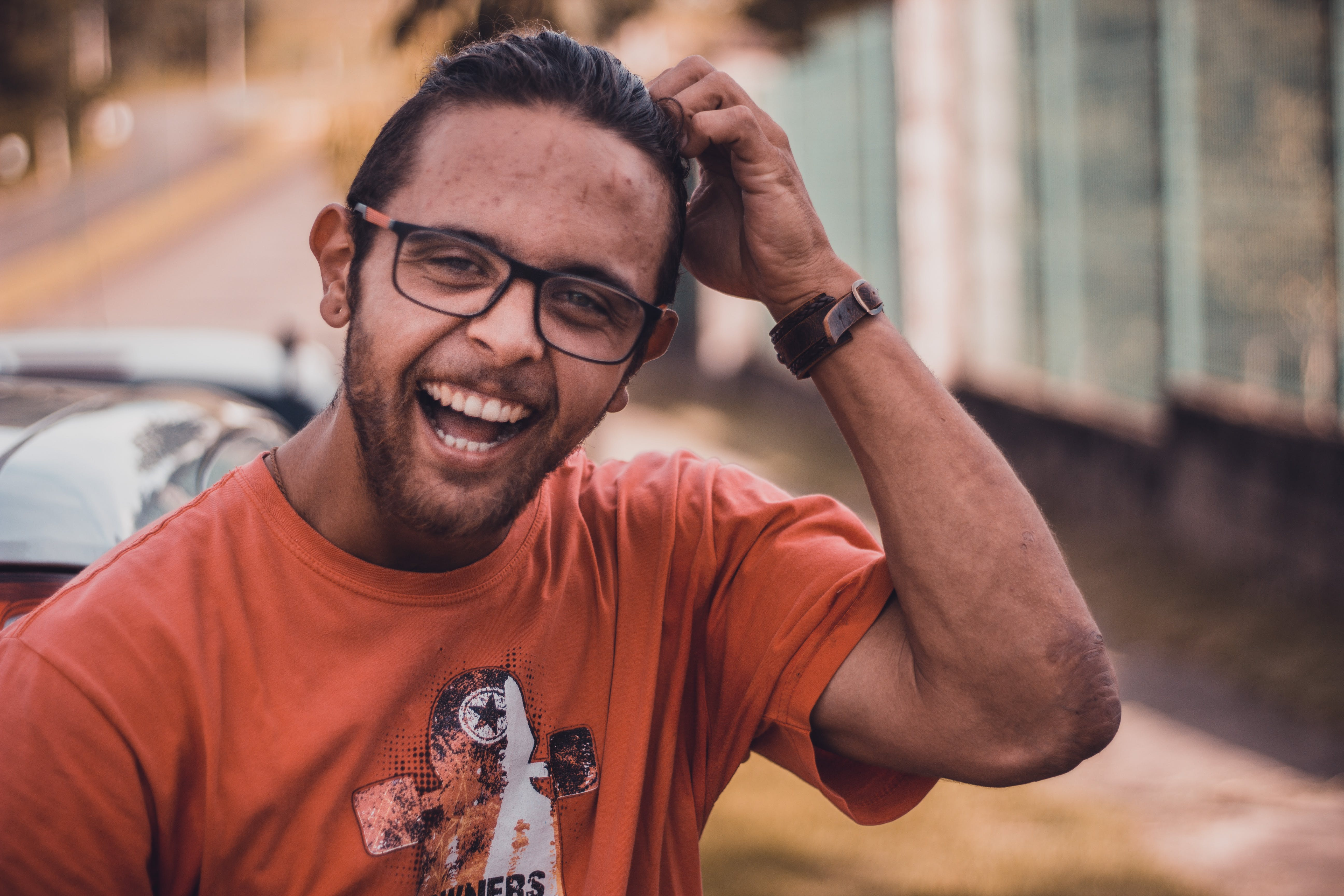 Selective Focus Photography of Man Smiling Putting Hands on Head