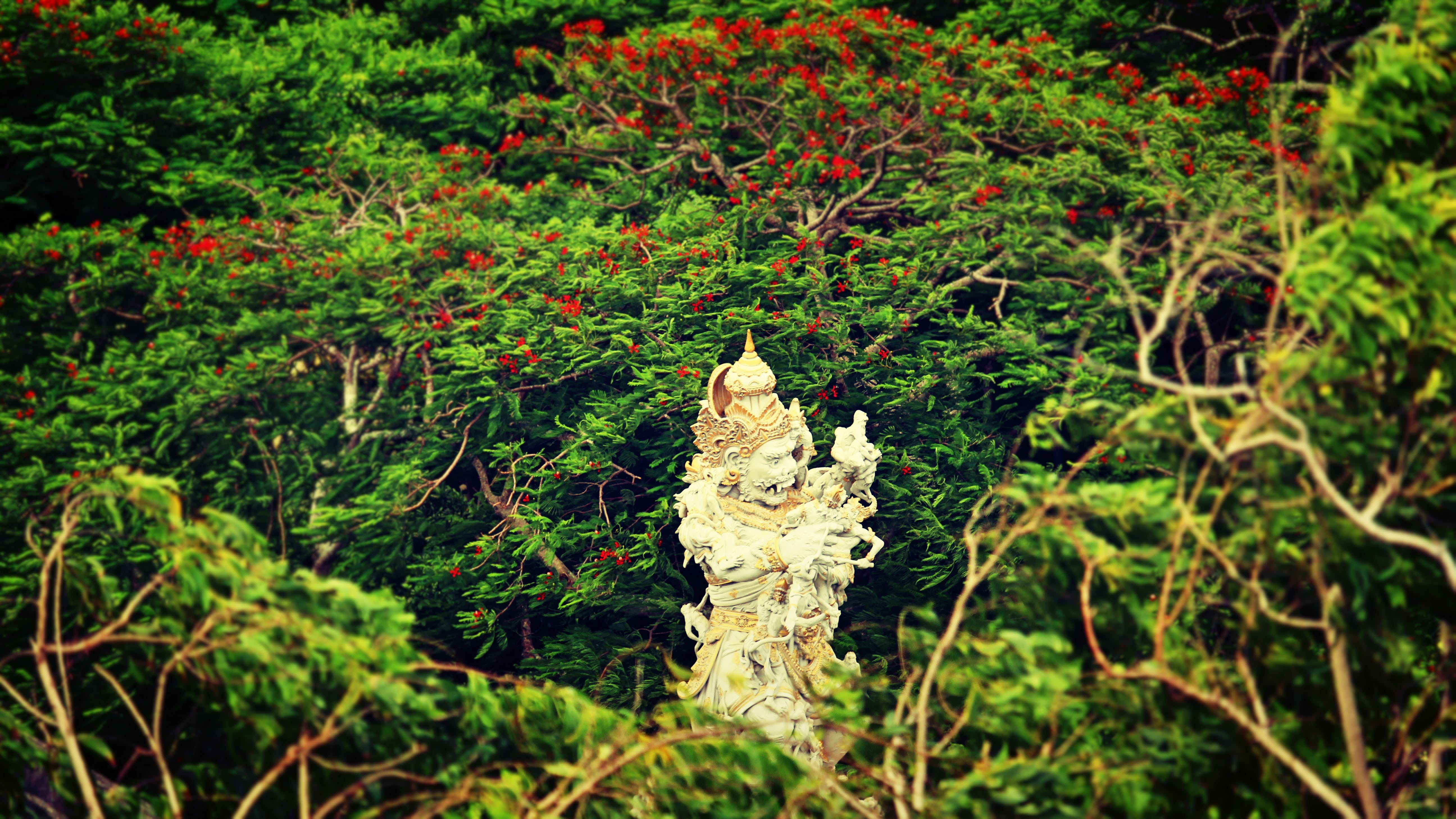 Beige Hindu Statue Surrounded by Trees at Daytime