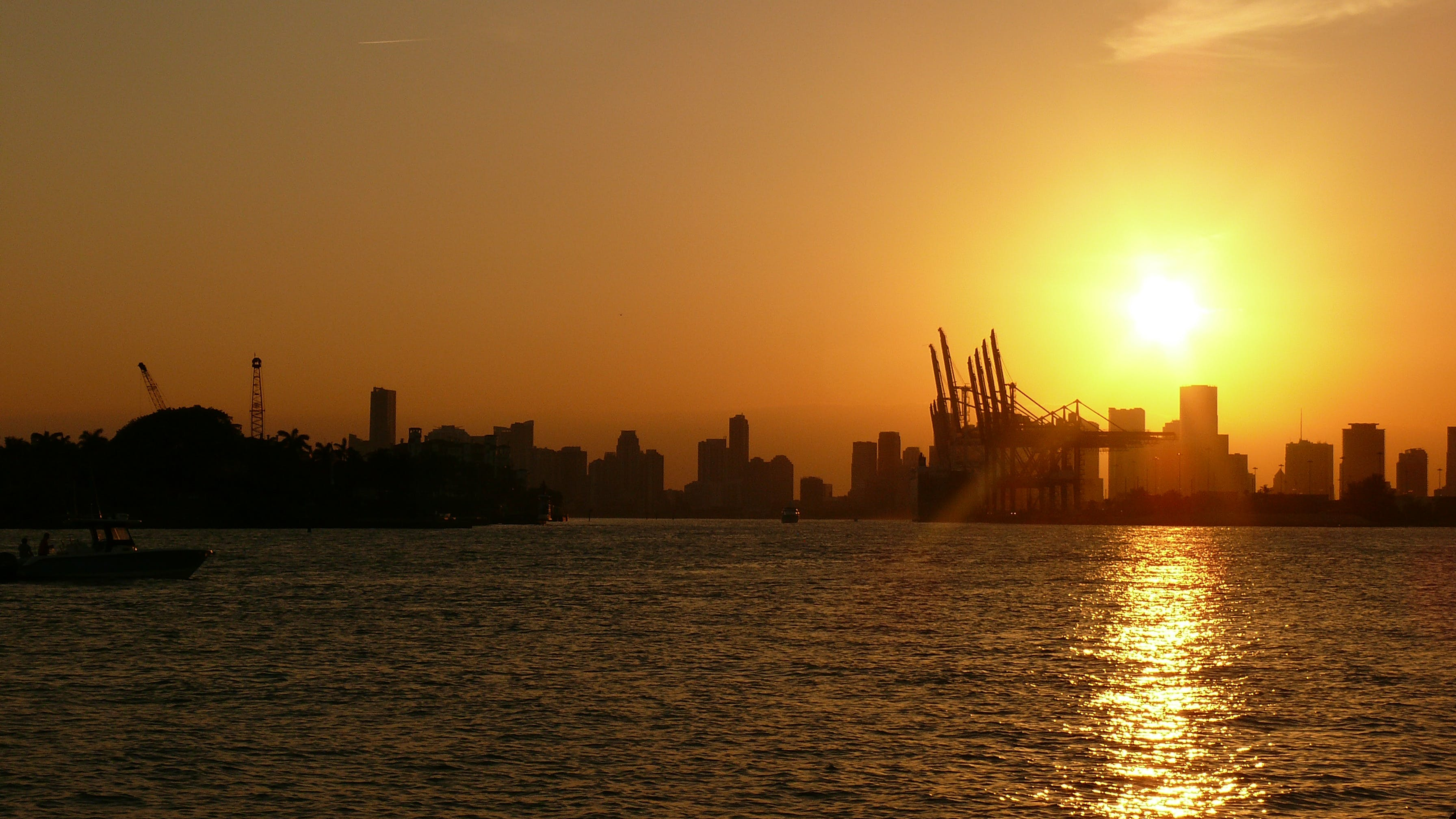 Silhouette of Buildings Near Body of Water Under Golden Hour