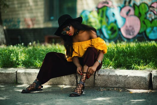 Woman Wearing Yellow Off-shoulder Top and Black Pants Sitting on Sidewalk Fixing Lace Sandals