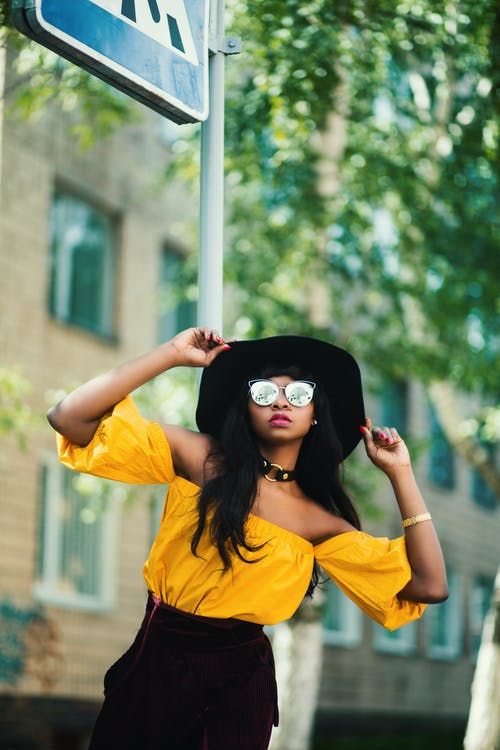 Woman in Black Hat and Yellow Top Taking Selfie