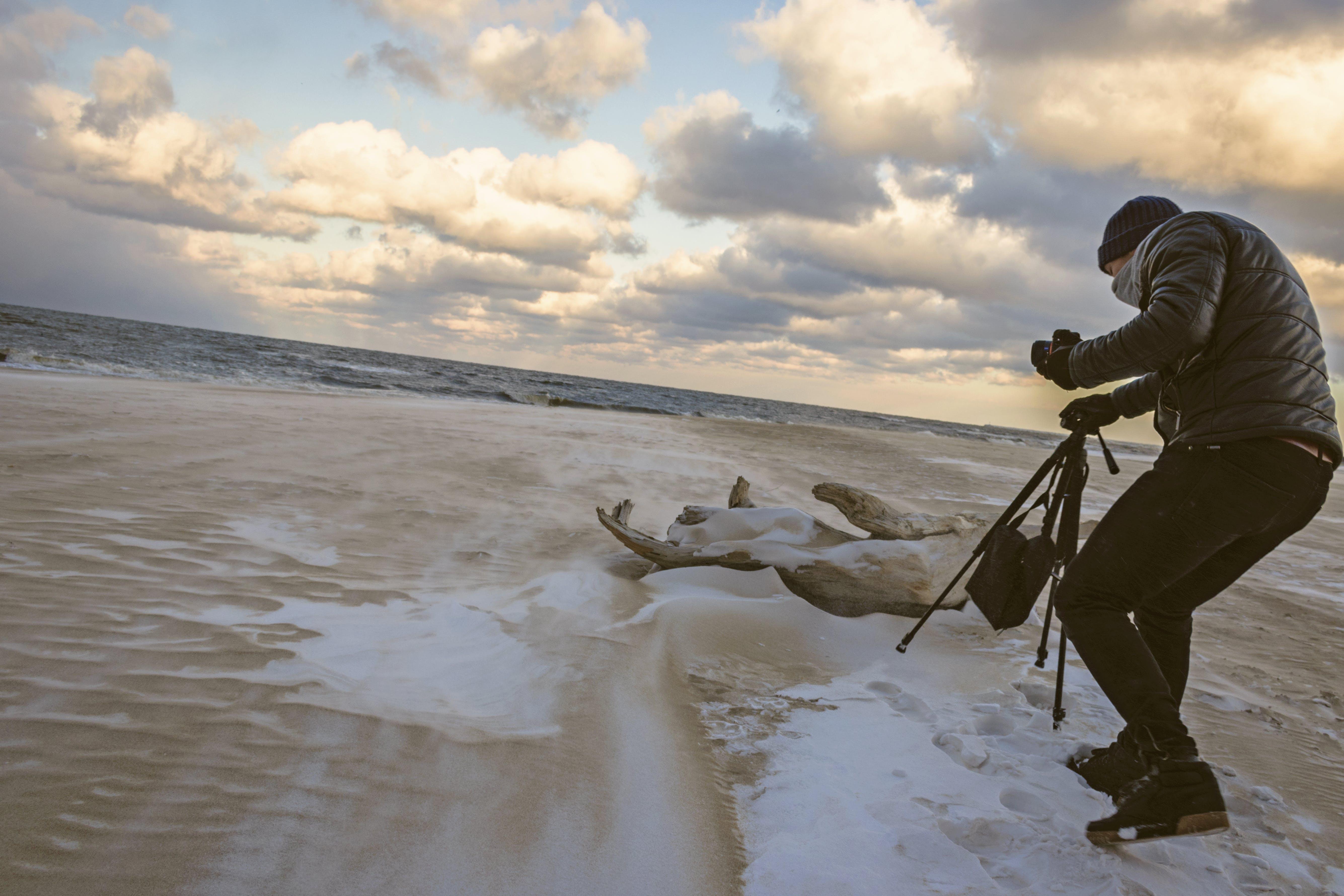 Man in Black Bubble Jacket Walking on Seashore While Holding Black Camera Tripod