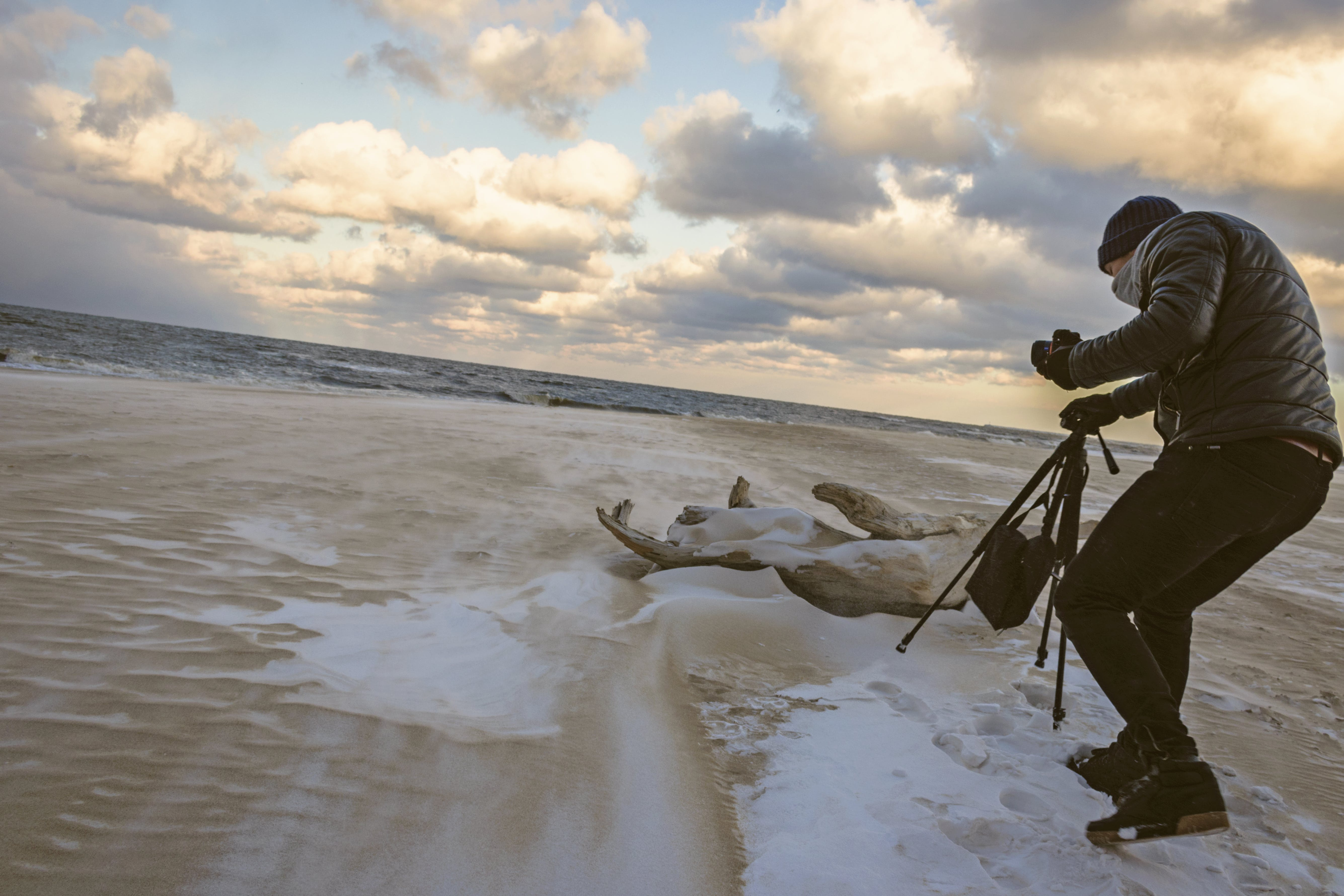 Man in Black Bubble Jacket Walking on Seashore While Holding Black Camera Tripod