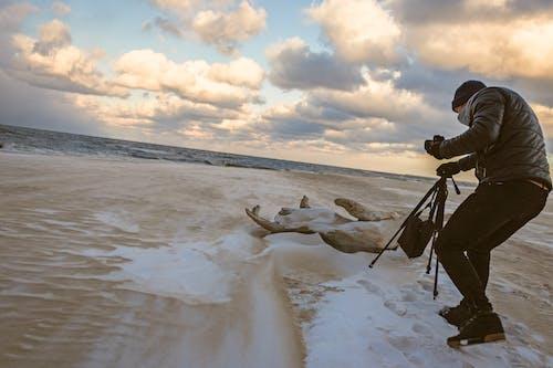 Hombre En Chaqueta De Burbuja Negra Caminando Por La Orilla Del Mar Mientras Sostiene El Trípode De Cámara Negro