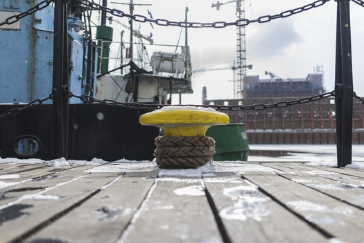 Yellow Anvil Beside Green Boat