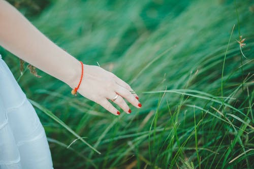 Woman Wearing White Skirt, Orange Bracelet, and Red Manicure Beside Green Grass