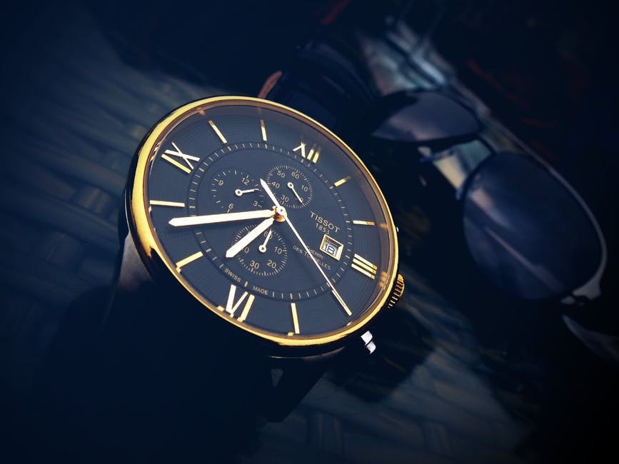 Round gold color chronograph watch with black strap at 7 36