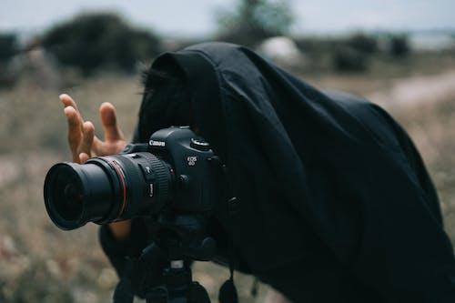 Person in Black Jacket Facing Black Canon Dslr Camera