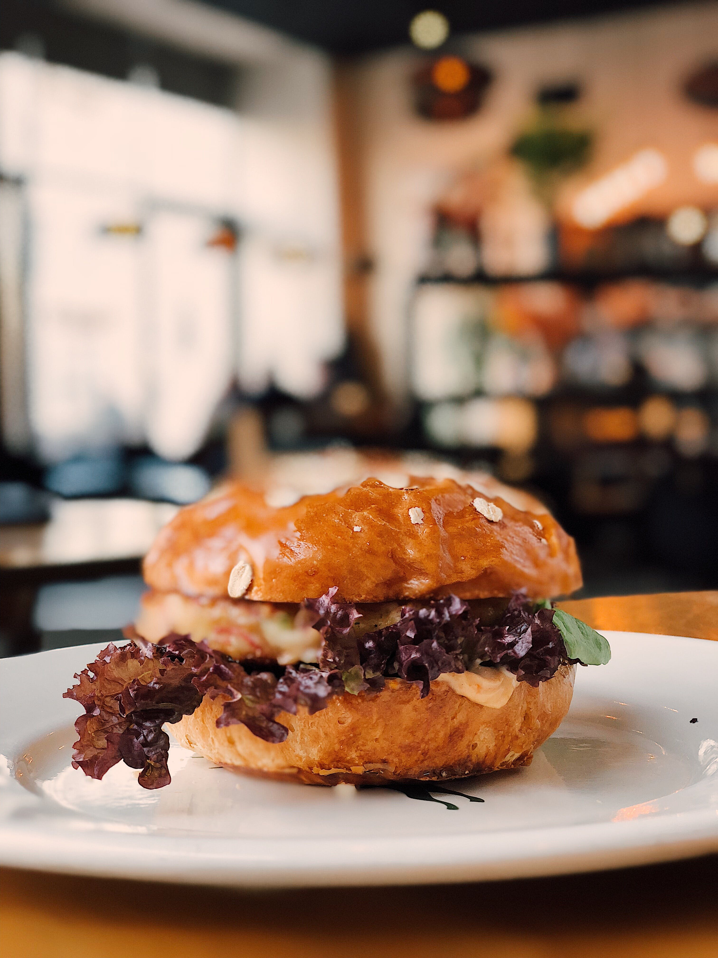 Selective Focus Photography of Burger on White Ceramic Plate