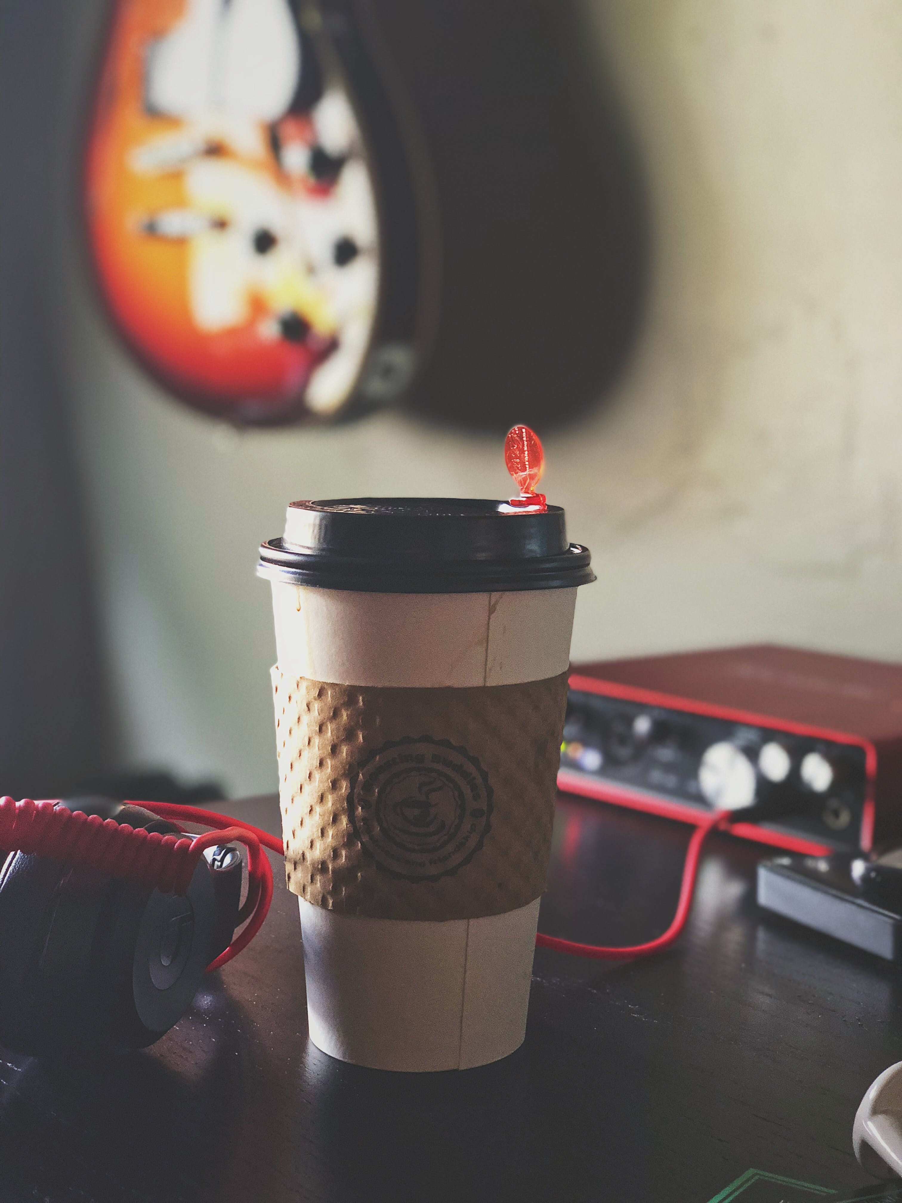 White and Brown Labeled Plastic Coffee Cup on Brown Tabletop Near Black Multimedia Player
