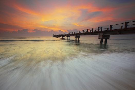 Brown Foot Bridge on Body of Water Under Orange Sky